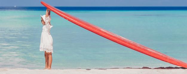 Aanbiddelijk meisje met rode grote surfplank op tropisch wit strand