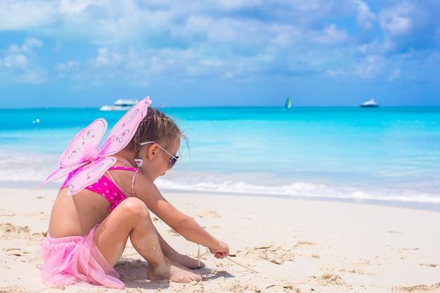 Aanbiddelijk meisje met vleugels zoals vlinder op strandvakantie