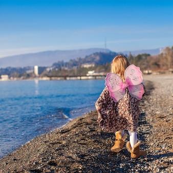 Aanbiddelijk meisje met vlindervleugels die langs het strand in een de winter zonnige dag lopen