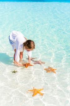 Aanbiddelijk meisje met zeesterren in water bij duidelijk water