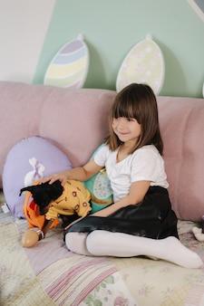 Aanbiddelijk meisje omhelst haar huisdier thuis op bankjonge geitje dat voor pasen thuis tijdens quarantaine voorbereidingen treft