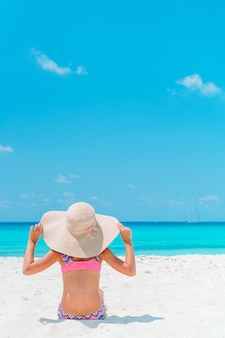 Aanbiddelijk meisje op het strand. gelukkig meisje geniet van zomervakantie de blauwe lucht en het turquoise water in de zee