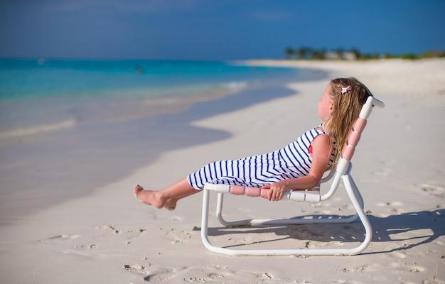 Aanbiddelijk meisje op ligstoel tijdens caraïbische vakantie