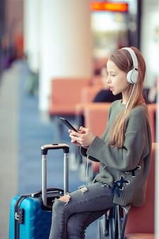 Aanbiddelijk meisje op luchthaven in grote internationale luchthaven dichtbij venster