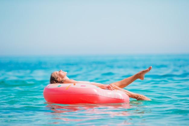 Aanbiddelijk meisje op opblaasbaar luchtbed in de zee