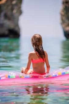 Aanbiddelijk meisje op opblaasbare luchtmatras in het overzees