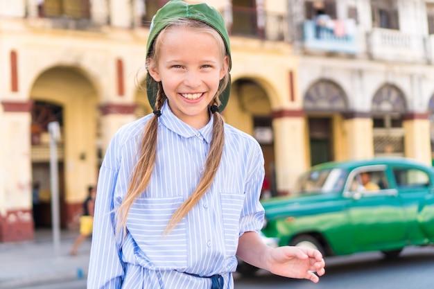 Aanbiddelijk meisje op populair gebied in oud havana, cuba. portret van jong geitje uitstekende klassieke amerikaanse auto als achtergrond