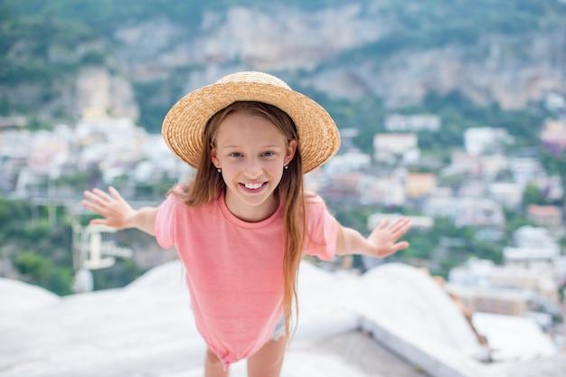 Aanbiddelijk meisje op warme en zonnige de zomerdag in positano-stad in italië