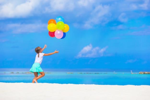 Aanbiddelijk meisje speelt met ballonnen op het strand