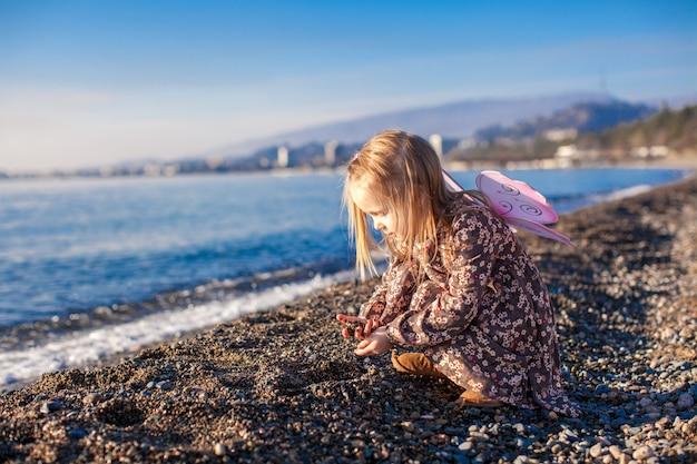 Aanbiddelijk meisje spelen op het strand in een zonnige winterdag