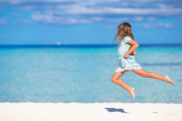 Aanbiddelijk meisje tijdens strandvakantie die pret heeft
