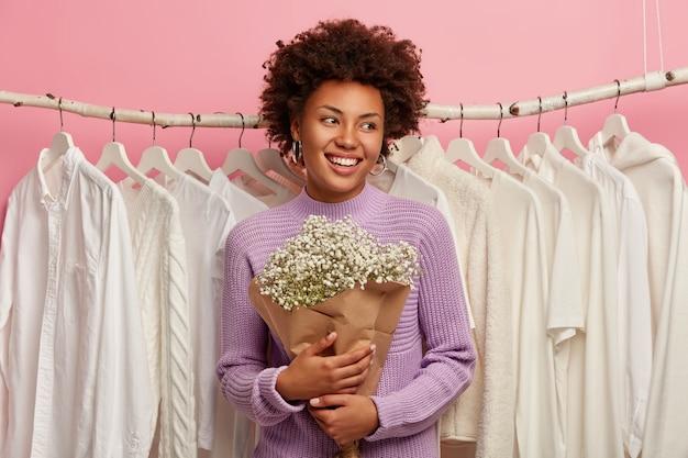 Aanbiddelijk model met donkere huid, gefocust opzij, heeft een aantrekkelijke glimlach, draagt een paarse trui, staat met boeket