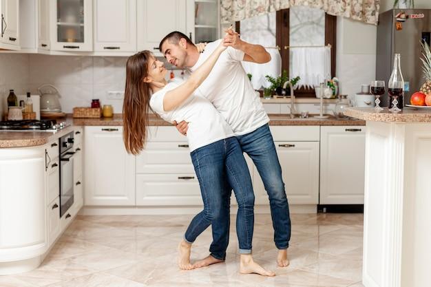 Aanbiddelijk paar dat in keuken danst