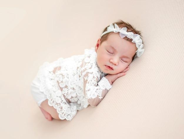 Aanbiddelijk pasgeboren babymeisje die mooi wit kostuum en krans dragen die op haar buik liggen en in studio slapen. schattige baby kind dutten hand in hand onder de wangen