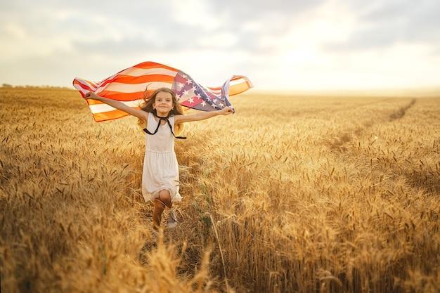 Aanbiddelijk patriottisch meisje dat in witte kleding een amerikaanse vlag draagt