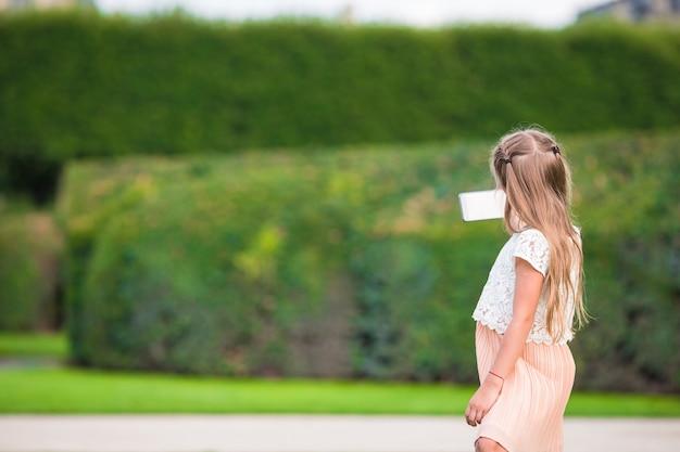 Aanbiddelijk peutermeisje met telefoon in parijs tijdens europese vakantie