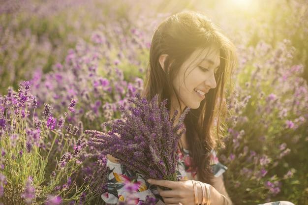 Aanbiddelijk romantisch portret van jonge vrouw rond lavendelbloemen.