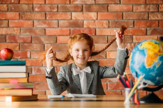 Aanbiddelijk schoolmeisje aan de tafel, vooraanzicht