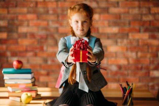 Aanbiddelijk schoolmeisje houdt een geschenk voor, vooraanzicht.