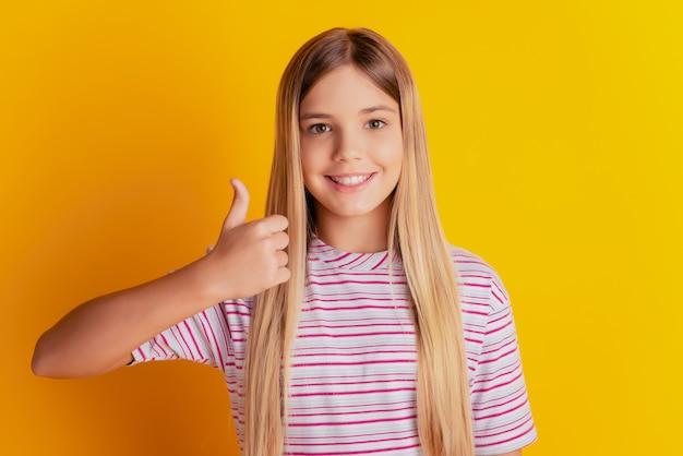 Aanbiddelijk steil blond pre-tienermeisje die thumbup tonen die op gele achtergrond wordt geïsoleerd