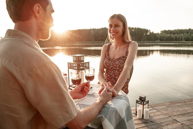 Aanbiddelijk stel brengt samen tijd door met het drinken van wijn op houten pier: knappe man houdt de hand van zijn vriendin vast, doet een huwelijksaanzoek, draagt verlovingsring, bosmeerachtergrond
