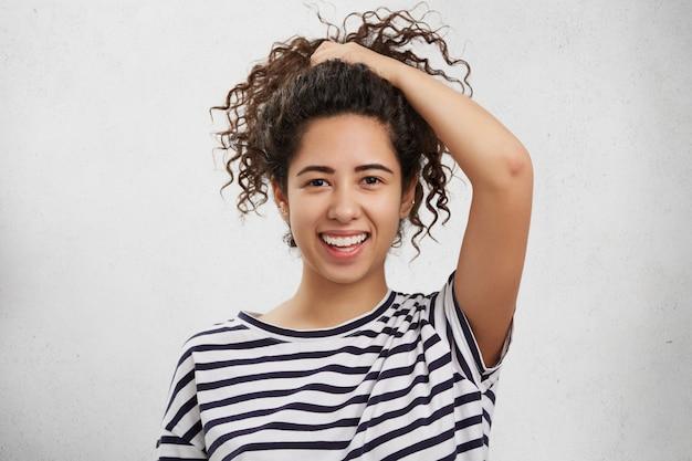 Aanbiddelijk tienermeisje met krullend haar, draagt een gestreept overhemd, maakt paardenstaart, adverteert mooi effect van nieuwe shampoo