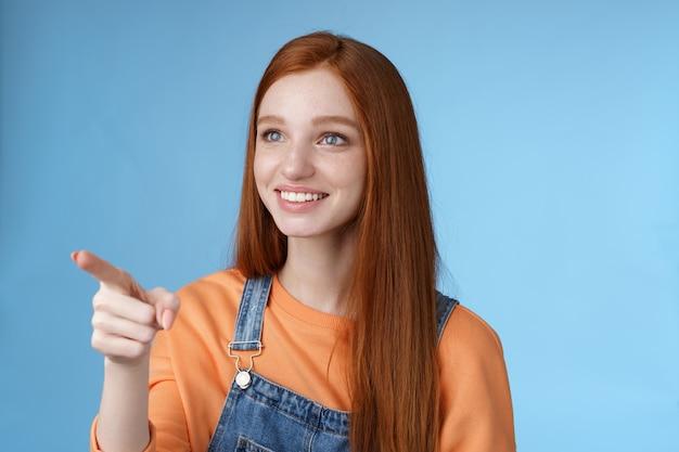 Aanbiddelijk vriendelijk zacht knap roodharige meisje kijk wijzend naar links geamuseerd glimlachen verbaasd zuchtend genegenheid aanbidden verbluffend adembenemend uitzicht blik gebiologeerd blauwe achtergrond