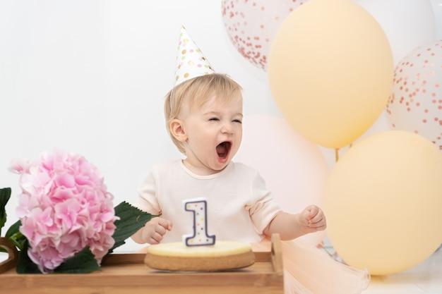 Aanbiddelijk, vrij gelukkig kaukasisch blond meisje dat schreeuwt om het eerste jaar te vieren