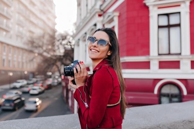 Aanbiddelijk vrouwelijk model dat foto van stad met camera neemt