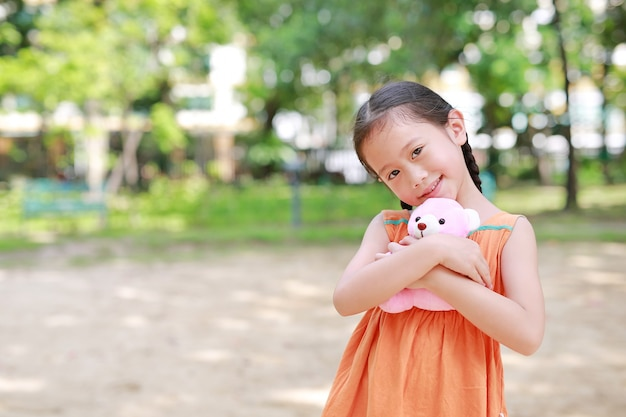 Aanbiddelijk weinig aziatisch kindmeisje die teddybeerpop in de tuin koesteren met het bekijken camera. sluit omhoog gelukkig jong geitje in de zomerpark.