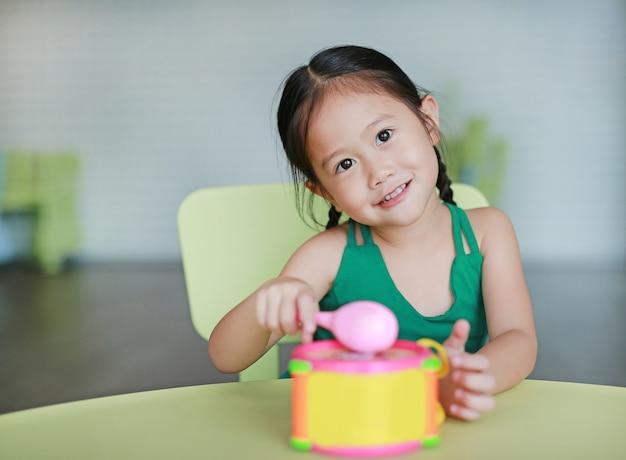 Aanbiddelijk weinig aziatisch spel die van het kindmeisje rakende stuk speelgoed trommel in kinderenruimte raken.