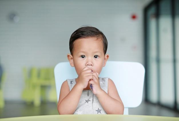 Aanbiddelijk weinig aziatische babyjongen die chocolade in het klaslokaal eet.