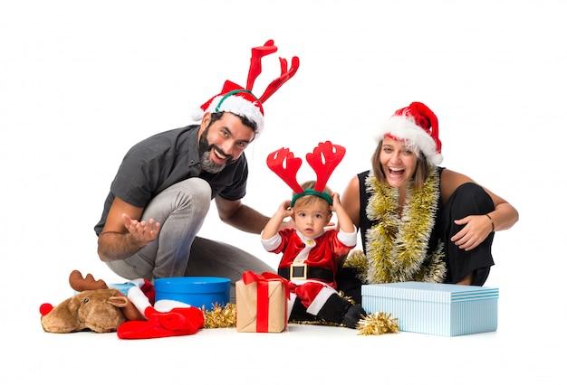 Aanbiddelijk weinig baby met zijn ouders bij kerstmispartijen op geïsoleerde witte achtergrond