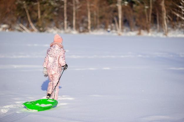 Aanbiddelijk weinig gelukkig meisje die in de winter sneeuwdag rodelen.