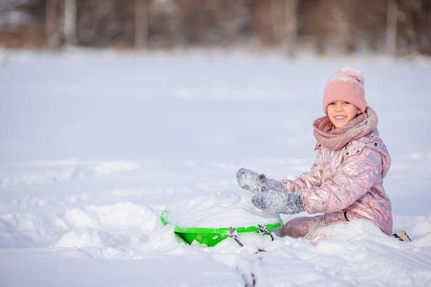 Aanbiddelijk weinig gelukkig meisje die in de winter sneeuwdag sleeën.