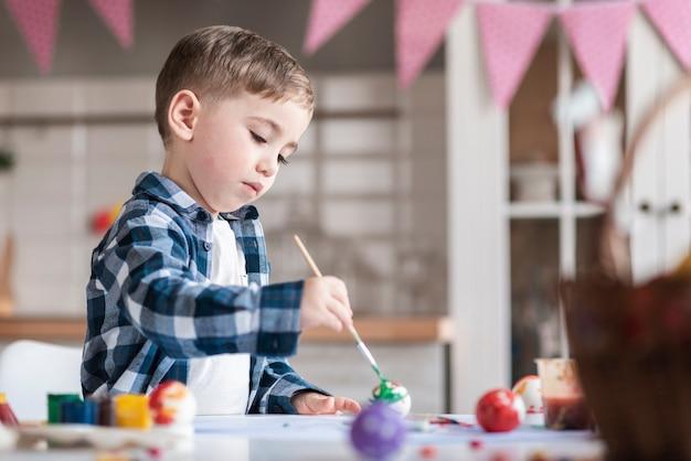 Aanbiddelijk weinig jongen die eieren schildert voor pasen