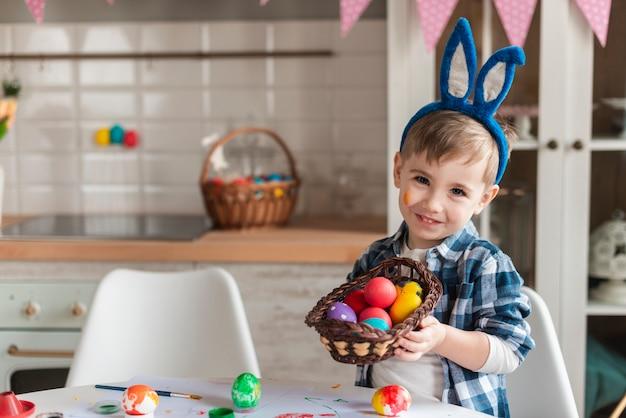 Aanbiddelijk weinig jongen die met konijntjesoren een mand met eieren houdt