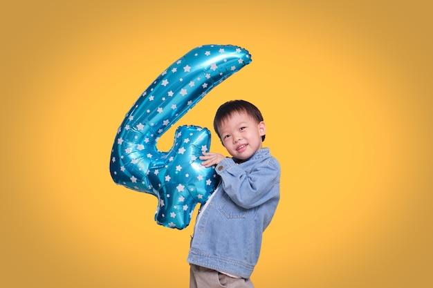 Aanbiddelijke aziatische vier éénjarigenjongen die zijn verjaardagsholding nummer 4 blauwe ballon op oranje achtergrond met het knippen van weg viert
