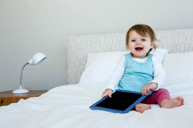 Aanbiddelijke baby die een tablet houdt en op een bed zit