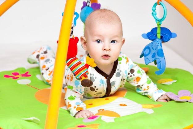 Aanbiddelijke baby die pret met speelgoed op kleurrijke speelmat heeft.