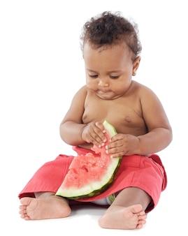Aanbiddelijke baby die watermeloen a over witte achtergrond eet