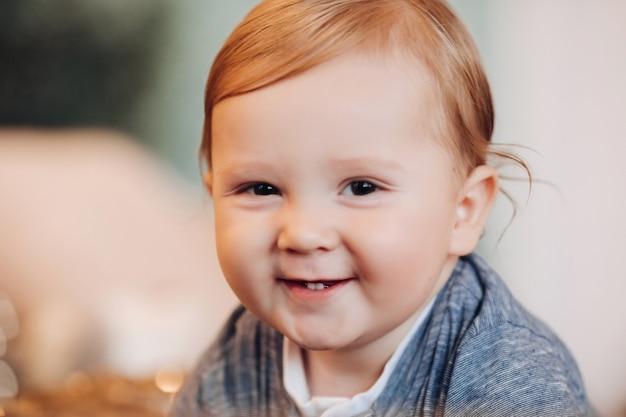 Aanbiddelijke babyjongen die bij camera glimlacht. wazige achtergrond.
