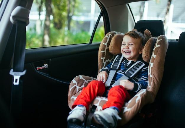 Aanbiddelijke babyjongen in een veiligheidsautozetel.