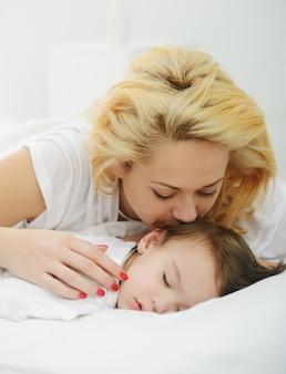 Aanbiddelijke babyjongen met mamma op bed