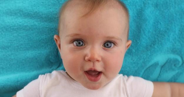 Aanbiddelijke blauwe eyed baby met geopende mond liggend op blauwe handdoek en camera te kijken