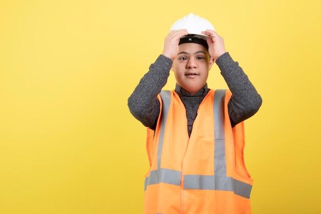 Aanbiddelijke bouwvakker in bouwvakker die zich over geel bevindt.
