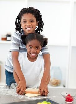 Aanbiddelijke broer en zuster kokende koekjes