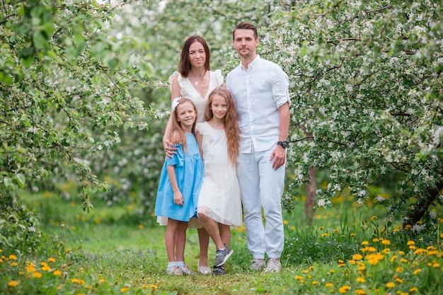 Aanbiddelijke familie in bloeiende kersentuin op mooie de lentedag