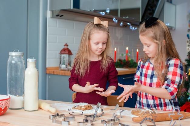 Aanbiddelijke gelukkige meisjes die de peperkoekkoekjes van kerstmis in kerstmisvooravond bakken