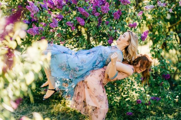 Aanbiddelijke gelukkige vrolijke vrolijke fabelachtige tweelingzusters in verschillende mooie zomerjurken die pret zoals kinderen in zonnig de zomerpark hebben.
